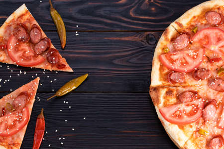 pizza with sausages and chili pepper on dark background, top view with copy space. Stok Fotoğraf