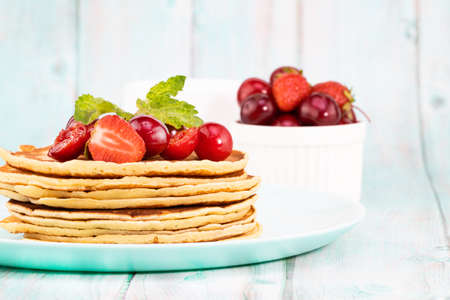Pancake breakfast. Homemade pancakes with fresh berry and honey, light background with copy space.