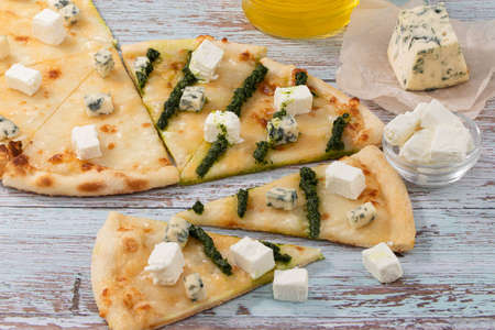 Slices of pizza four cheeses with pesto on a wooden background. Stok Fotoğraf