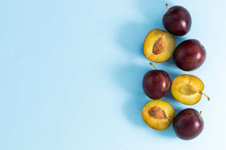 plum slices on a blue background. Top view with copy space. Фото со стока