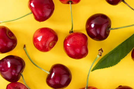 Cherries pattern on yellow background. Top view. Flat lay.