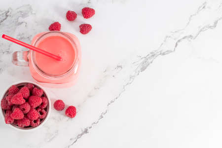 Berry smoothie in a glass jar on the breakfast with raspberries. Top view with copy space. Фото со стока