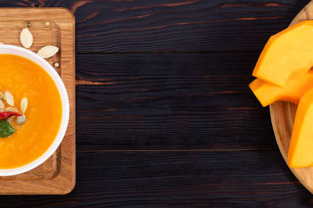 Pumpkin and carrot soup with cream and pumpkin seeds on wooden background with copy space. Top view. Фото со стока