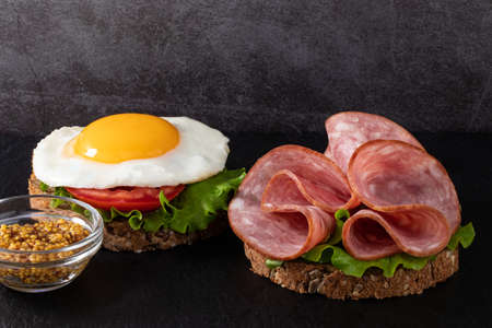 ham and egg bacon sandwich on dark wooden background with copy space