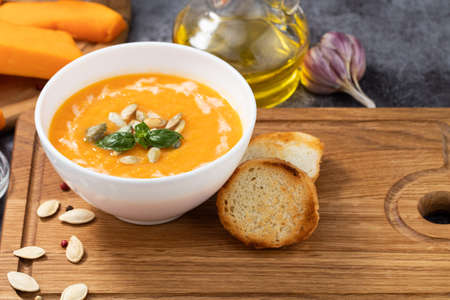 Pumpkin and carrot soup with cream and pumpkin seeds on wooden background.