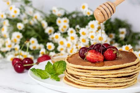 Homemade pancakes with fresh berry and honey. Summer breakfast. Фото со стока