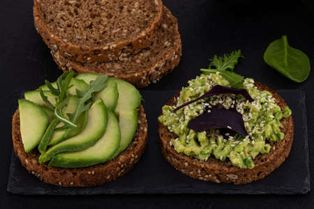 Avocado sandwich on dark rye bread on  dark