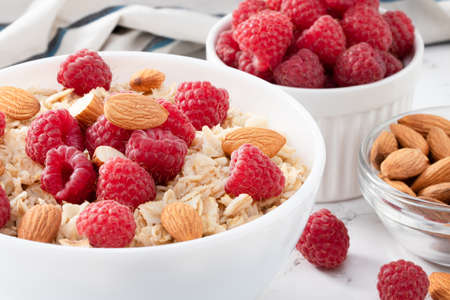 bowl of oatmeal with raspberries and almonds.