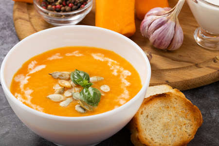 Pumpkin cream soup with seeds on a stone background.