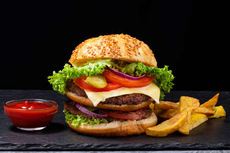 Big burger with french fries on dark background. Фото со стока