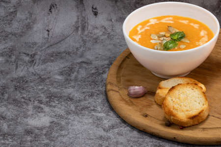 Pumpkin cream soup with seeds on a stone background, with copy space.