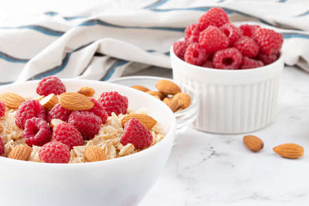 Healthy breakfast. Bowl with oatmeal with fresh raspberries and almonds.
