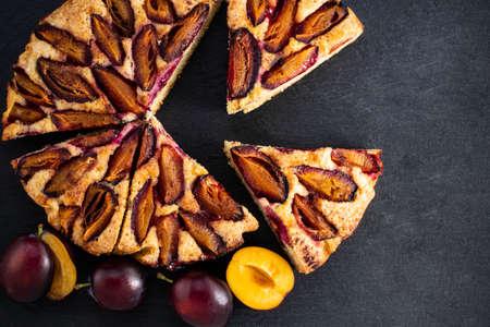 plum cake on dark background top view.