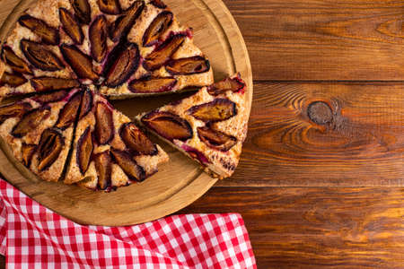 plum cake on wood background with copy space.