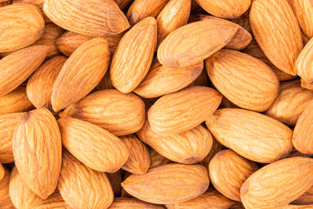 Almond background texture. Background of raw almond nut located randomly.