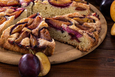 plum pie on a rustic wood background with plums.