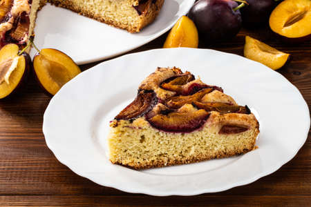 slice of plum cake and plum pie on a rustic wood background with plums.