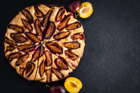 plum cake on dark background with copy space, top view.