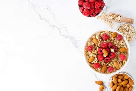 Healthy breakfast. Bowl with oatmeal with fresh raspberries and almonds. Copy space.