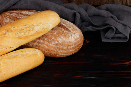baked bread and baguette on wooden table background. Фото со стока
