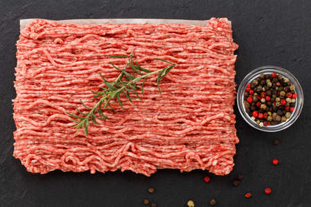 raw minced meat and spices on dark background., top view.