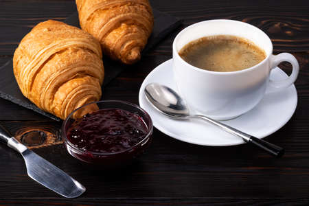 fresh croissants with jam and coffee on dark background. French breakfast. Фото со стока