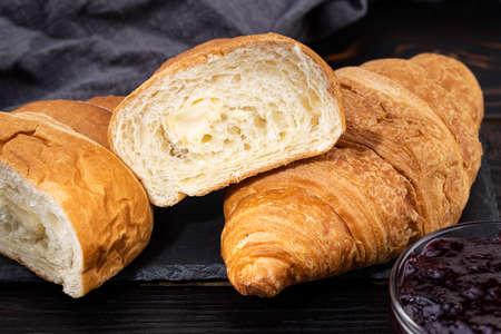 fresh croissants with jam on dark background.