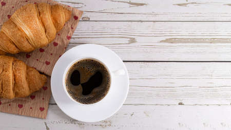 fresh croissants and coffee on light wooden background with copy space.