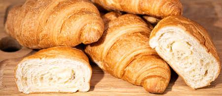 fresh croissants on wooden board on a dark background. Фото со стока
