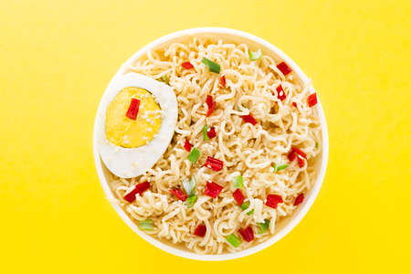 noodles with vegetables and egg in bowl on yellow background top view with copy spaces.