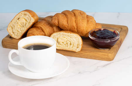 fresh pastries and coffee. Croissant with jam and a cup of coffee