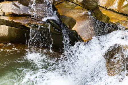 bubbling water and stones. Falling waterfall. Background texture.