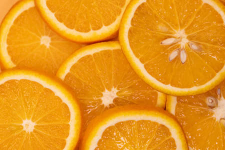 slices of orange fruit, top view. Orange background texture.
