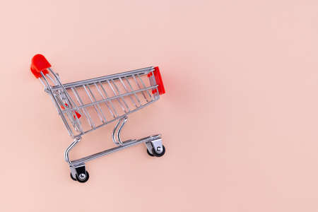 Shopping cart on beige background. Top view with copy space. Shop trolley at supermarket. Sale, discount, shopaholism concept. Consumer society trend.
