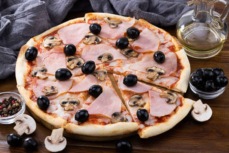 pizza and pizza ingredients. Olives, mushrooms and pizza on a dark background. Фото со стока