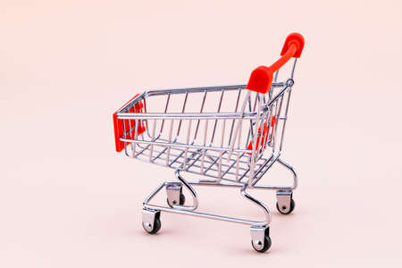 Shopping cart on beige background. Shop trolley at supermarket. Sale, discount, shopaholism concept. Consumer society trend.