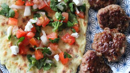 Photo plates with food Afghan flatbread with capers, meatballs and Salsa sauce Top view Stock Photo