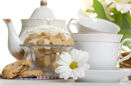 Teacups and flower on table against teapot