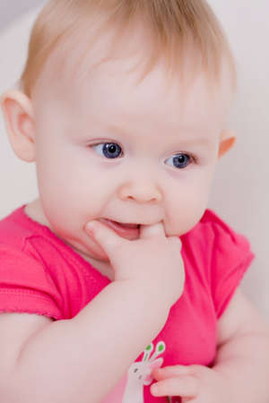 nappy new year: Soft focus portrait of beautiful little baby girl touching her teeth