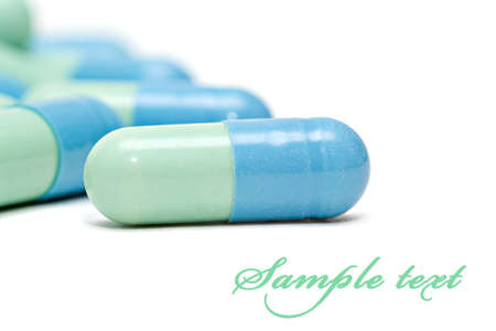 Blue-green pills isolated over white background