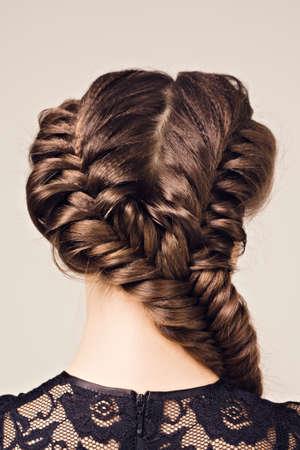 Frisur Porträt der schönen Brünette Mädchen mit kreativen Frisur Zopf im schwarzen Kleid Standard-Bild