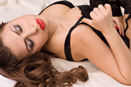 Beautiful sensuality woman with red lips lying in bed in her underwear. Stock Photo