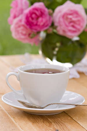 White teacup on wooden table in spring garden photo