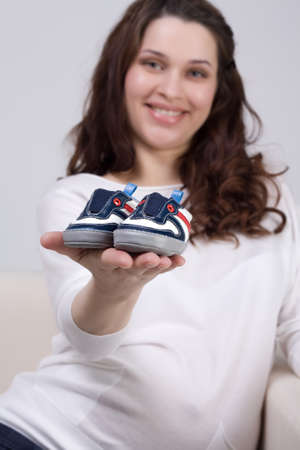 Pregnant woman holding pair a babys bootees photo