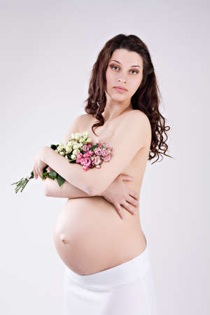 beautiful pregnant woman with bouquet of roses photo