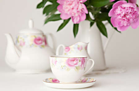 Tea set and pink peonies in jar on white background  Natural light photo