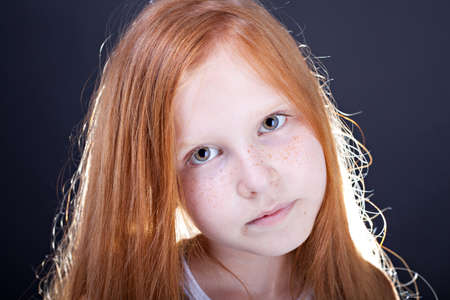 Portrait of a red haired girl on dark background