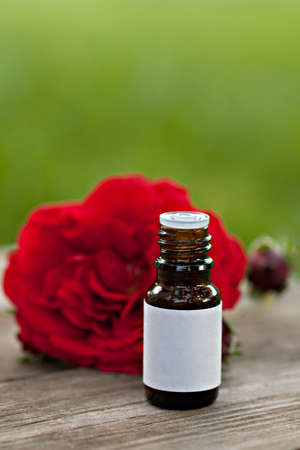Bottles of essential oil and red rose on wooden background outdoor photo