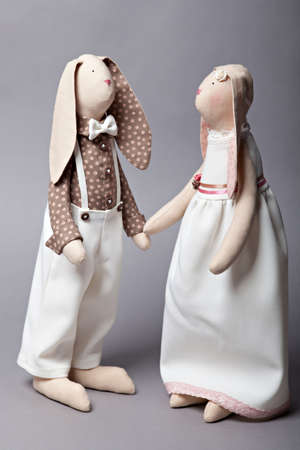 Wedding rabbits on grey background. Handmade soft toys