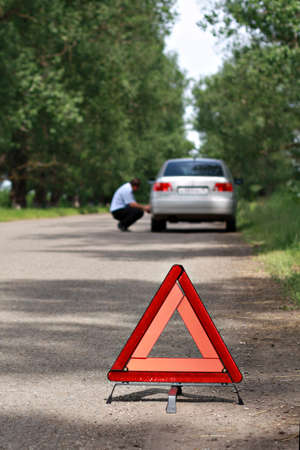 non urban: The image of emergency stop sign under the foreground and man near car under background  Focus is under the sign